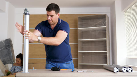Husband assembling furniture in new house Archivo