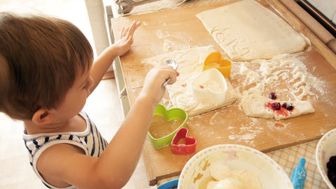 4k video of little funny boy playing with dough and ingredients on kitchen Footage