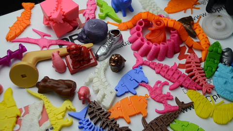 Many bright multi-colored objects printed on 3d printer lie on flat surface Footage