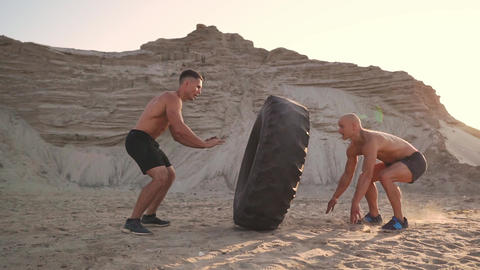 Two athletes train in active mode on the beach doing push-UPS and pushing a huge Live Action