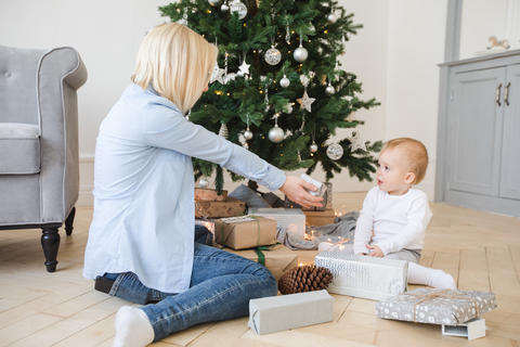 Young woman sitting near Christmas tree with little boy フォト