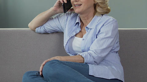 Female pensioner sitting on sofa, having conversation over phone, call to friend Live Action