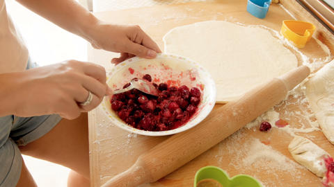 Closeup 4k footage of young woman mixing and preparing sweet cherry filling for Footage