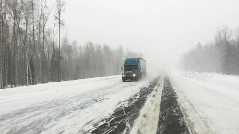 The car is on a snow-covered highway. Heavy truck with trailer carries cargo. Footage