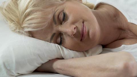 Head of senior woman lying on pillow, light smile on her face, undisturbed sleep Footage