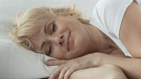 Aged woman lying in bed with head resting on pillow, smiling, comfortable sleep Footage