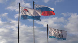 Waving flags on flagstaff: flag of Russia, flag of Kamchatka, Petropavlovsk City Footage