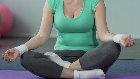 Elderly woman sitting on yoga mat cross-legged, body wellness, inner balance Footage