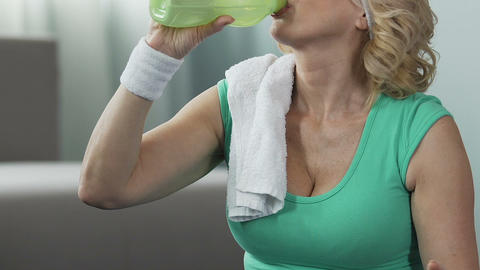 Female pensioner taking deep breath and drinking water, active life position Live Action