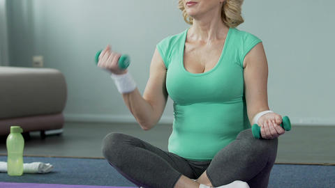 Aged woman sitting on floor cross-legged, flexing arms holding dumbbells, sport Footage