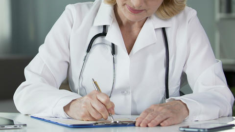 Female physician prescribing medication at clinic, professional doctor at work Footage