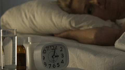 Ill female pensioner lying in bed and suffering from insomnia, health problems Live Action