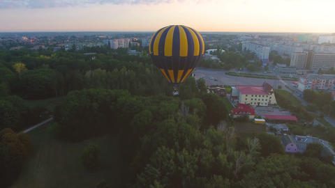 Hot air balloon floating over city green area in morning, escape from routine Live Action