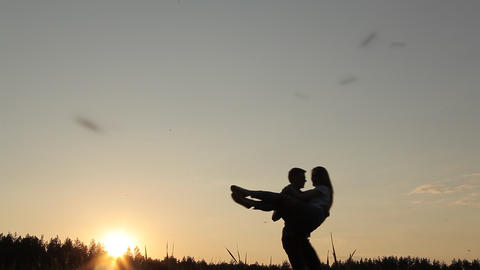 A guy turns a girl in her arms in the evening Archivo