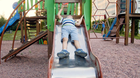 4k video of funny little toddler boy sliding down on slide at playground Live Action