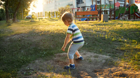 4k footage of little toddelr boy playing on playground at park and throwing sand Footage