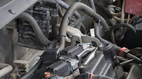 Hands of mechanic man removing car spark plug coil socket Footage