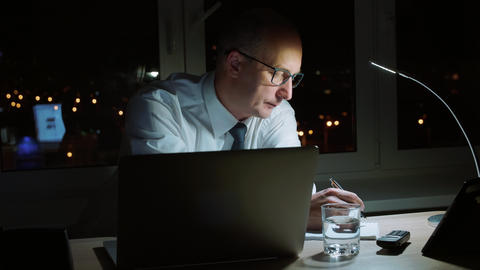 Executive businessman writing note in notebook at table in night office Footage