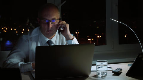 Adult businessman calling to mobile phone while overtime work in night office Footage