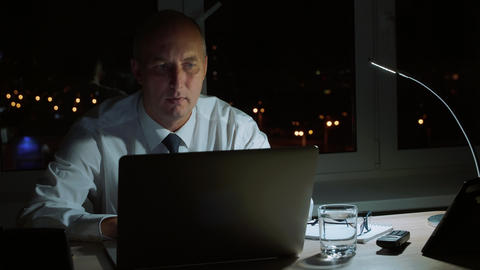 Focused businessman taking eyeglasses and working to laptop in night office Footage