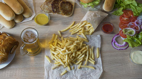 Man pouring french fries in sauce and drinking beer, unhealthy eating, calories Live Action