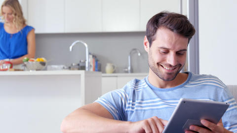 Smiling man using tablet with his wife behind him preparing the meal Footage
