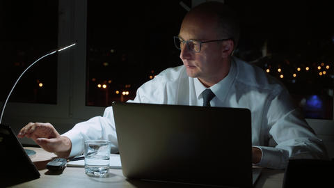 Executive businessman using tablet pc and working on notebook in night office Footage