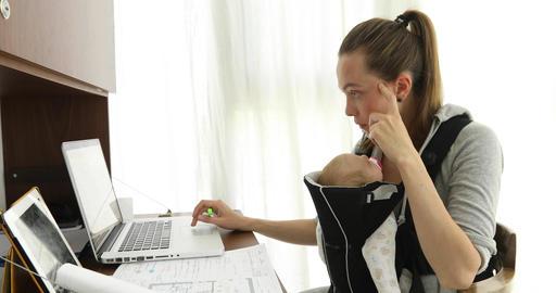 Woman working, nursing newborn baby Archivo