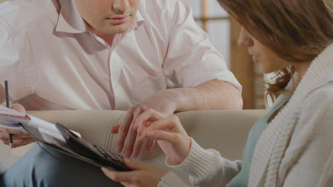 Couple carrying out calculations planning big purchase, estimation of expenses Live Action