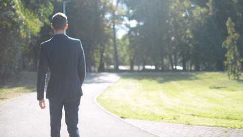 Young businessman walking forward in a hurry to job interview or meeting, back Footage