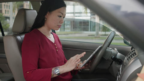 Busy Chinese Business Woman Working In Car With Papers GIF