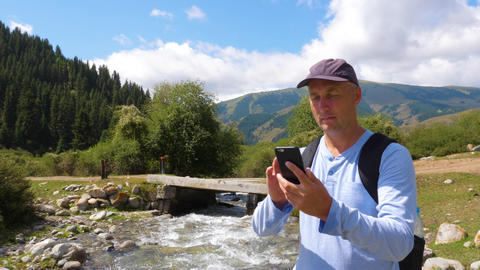 Man using smart phone for video chat while travel in mountain with rapid river Footage