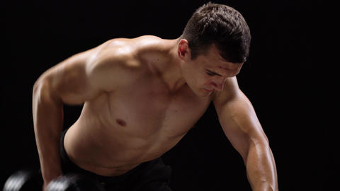 Man flexes his hands with dumbbells, training his back on a black background in Footage