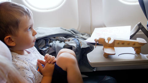 4k video little toddler boy looking at woodent airplane toy during flight in Archivo