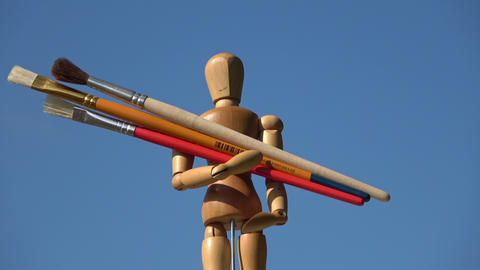 Rotating wooden artist manikin mannequin and holding three paintbrushes Footage