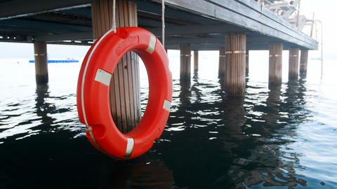 4k footage of life saving red buoy or ring hanging on wooden pier at sea beach Live Action