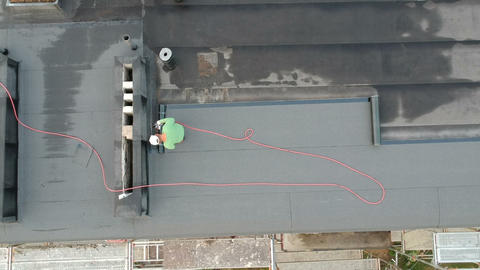 Worker repair flat house roof, aerial view Live Action