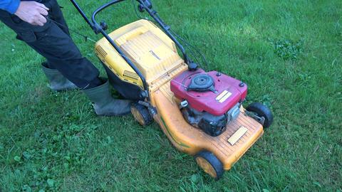gardener starting lawn mower on garden grass Live Action