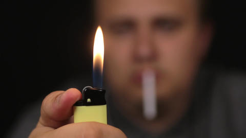 Close-up, man sets a gas lighter on fire. Focus on the lighter Footage