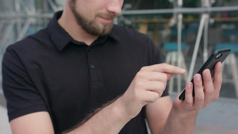 Man with Beard Using a Phone in Town Photo