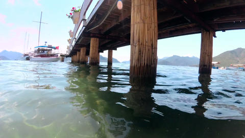 Slow mtoion footage of calm sea and old wooden pier on seashore Footage