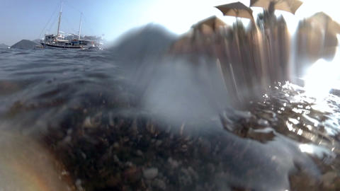Closeup slow motion footage of wave with sand and weeds rooling over sea shore Footage