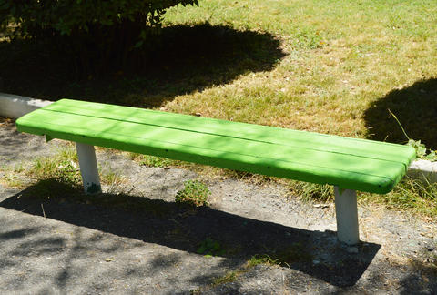 Wooden painted bench along the paths in the summer Park on a Sunny day Photo