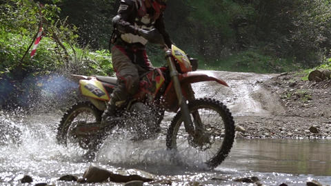 Motocross Rider Crosses the Water Barrier. Slow Motion Footage