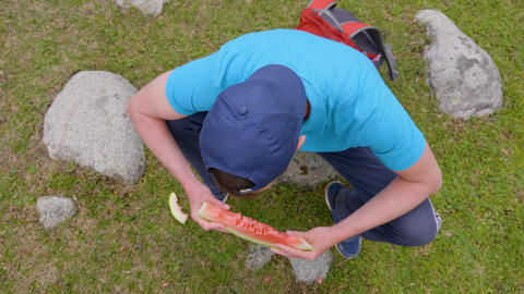 Man eating slice of sweet juicy watermelon and smiling outdoors, high angle view Live Action