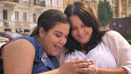 Two big caucasian females smiling at smartphone swiping while sitting on bench Footage