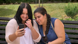 Two young obese girls waving in camera on smartphone and smiling with relax on Footage