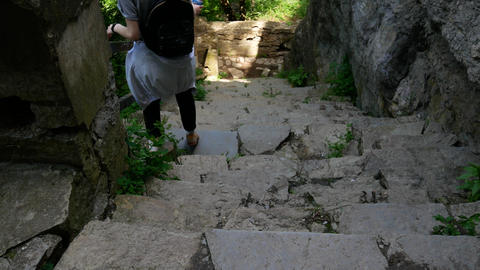 A young girl hiker descends the mountain steps 영상물