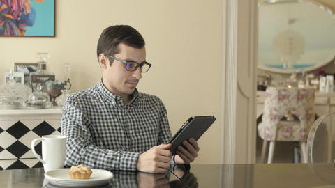 A Young Man Looks Through His Tablet as He Hakes Footage