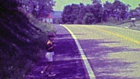 1968: Boy walking to 1st day of school down country road waves goodbye Footage